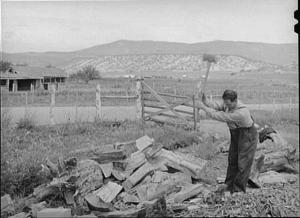 A sepia photograph of a man chopping wood.